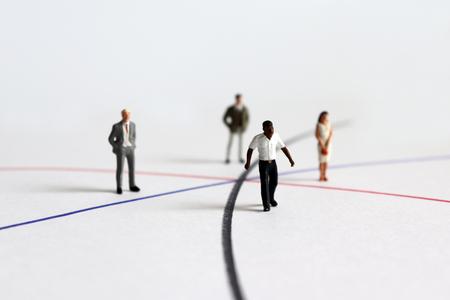Personas diversas en miniatura de pie en una línea diferente. Foto de archivo