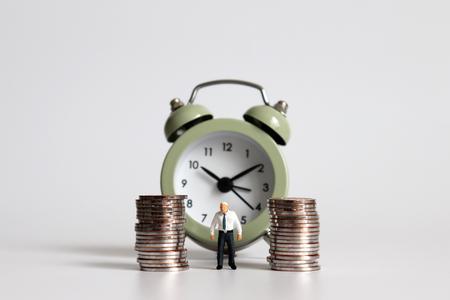 Uomo anziano in miniatura in piedi con una pila di monete davanti alla sveglia.
