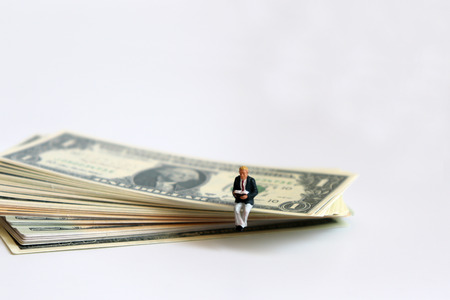 A miniature man reading a book on the US dollar. Stock Photo