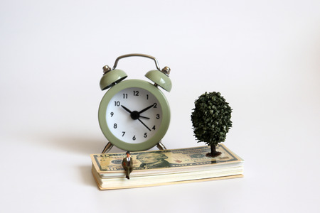 A miniature man sitting on the dollar and an alarm clock.