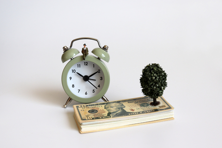 A miniature man sitting on the alarm clock and dollar.