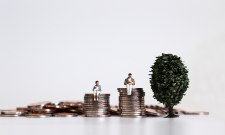 Miniature man and miniature woman with baby sitting on a pile of coins. Stock Photo