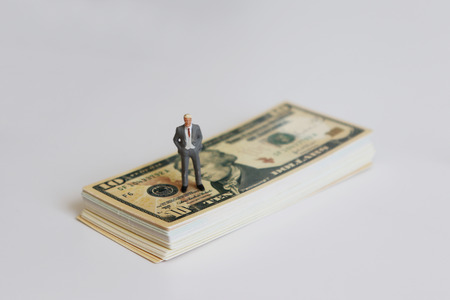 A miniature man standing on the dollar.