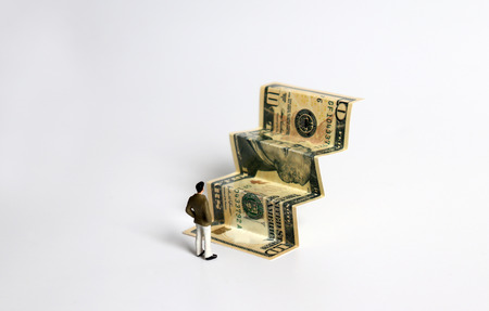 The banknotes are folded in a stair pattern and the miniatures man. Stock Photo