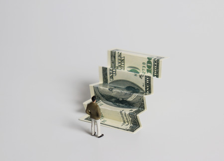 The back of a miniature man standing in front of a bill folded in steps.