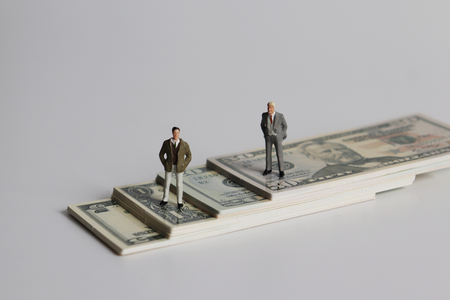 Two miniature men standing on a pile of bills.