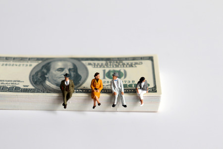 Miniature people sitting on a pile of bills.