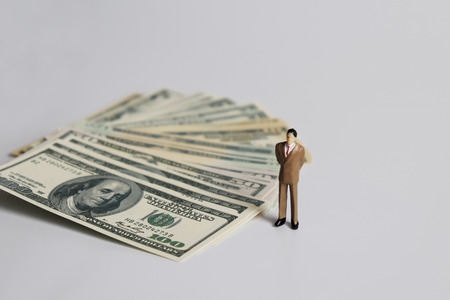 Miniature businessman standing next to the pile of dollars. Stock Photo