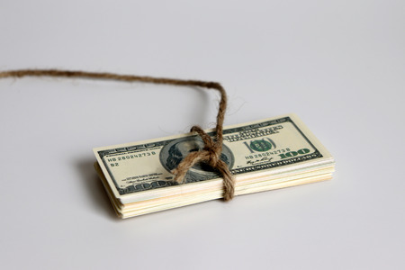 The pile of dollar banknote wrapped in a rope.