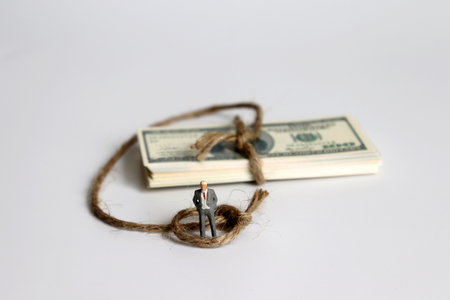 The pile of dollar banknote with a miniature man wrapped in a rope.