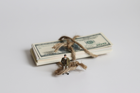 The pile of dollar banknote with a miniature young man wrapped in a rope.