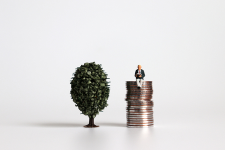 A miniature tree next to a miniature man sitting on a pile of coins. Stock Photo