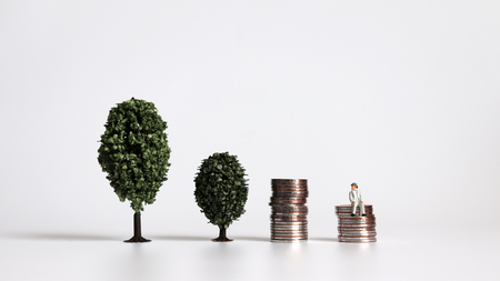 Two trees side by side with a miniature man sitting on a pile of coins.