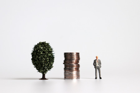 A miniature man standing next to a pile of coins and a tree. Stock Photo