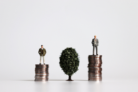 Two miniature men standing on a pile of coins on either side of a tree.