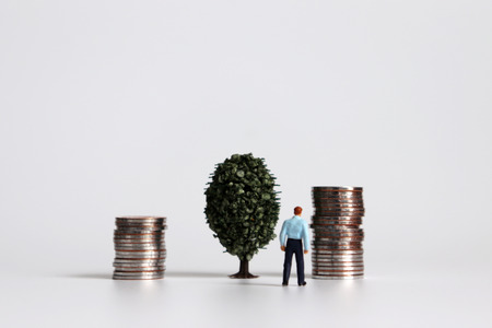 A miniature man with a pile of coins and wood. Stock Photo