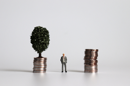 Miniature man standing between a pile of coins and a tree on a pile of coins. Stock Photo