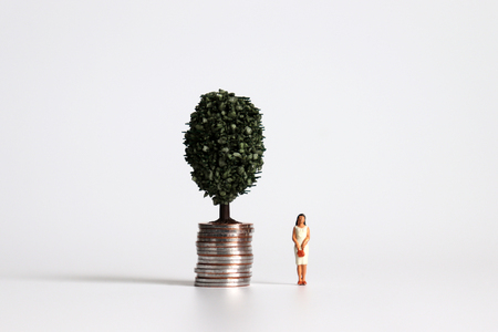A miniature woman standing next to a pile of coins with trees.