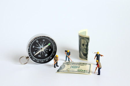 A compass next to a hundred dollar bill torn in half with a miniature worker. Stock Photo