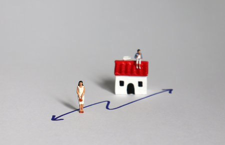 Miniature women on two different paths.