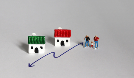 A concept of gay family and social conflict. Miniature people and miniature houses.