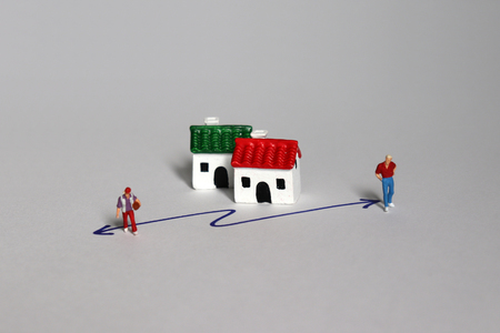 Miniature people and miniature houses. A concept of single-person household growth and social problems. Stock Photo
