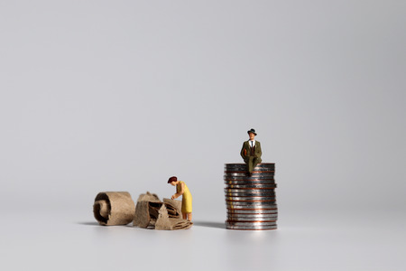 A pile of coins and miniature people. A concept of profit and poverty. Stock Photo