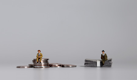 A miniature man sitting on a pile of coins and a miniature man sitting on a pile of bills. Stock Photo