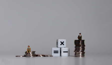 Two miniature men sitting on a pile of coins and three math symbol cubes.