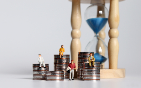 The miniature people and pile of coins. The concept of time and income poverty.