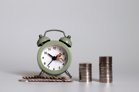 Miniature people and coins hanging on the clock hands. Imagens