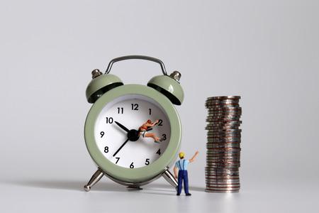 Une personne miniature avec un réveil et une pile de pièces. Un concept de société compétitive et de revenu. Banque d'images