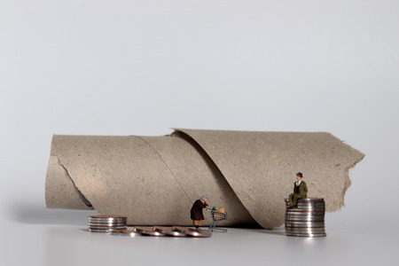 The concept of the gap between rich and poor. A pile of miniature people and coins.