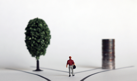 Miniature man with a pile of wood and coins on each of two roads.