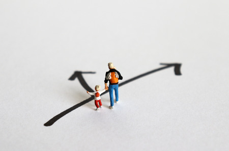 Concept of role conflict. A miniature man and his children standing at a crossroads. Imagens