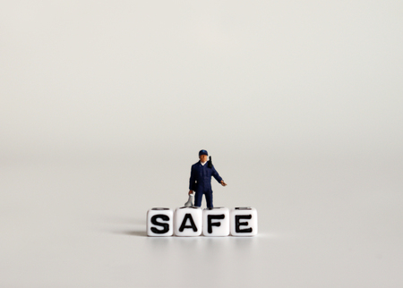SAFE word written in white cube. Miniature combat police with letter cubes.