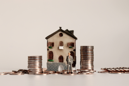 Miniature people with a pile of coins in front of the miniature house.