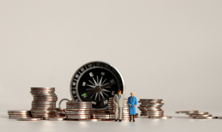 Compass and pile of coins. A miniature old couple.