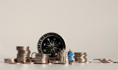Kompas i stos monet. Miniaturowa para staruszków.