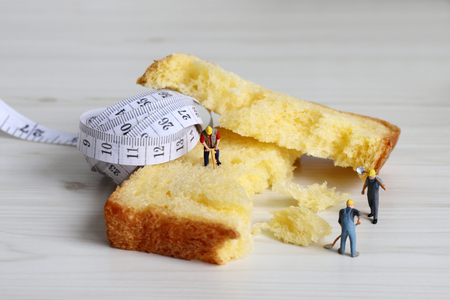 Tape measure and miniature workers on the bread. A concept about reducing carbohydrate intake.