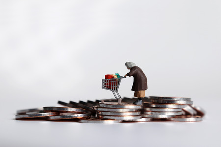 A miniature woman pulling a cart on a pile of coins.