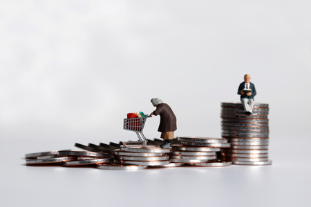 A miniature woman pulling a pile of coins and a miniature man sitting on a pile of coins.