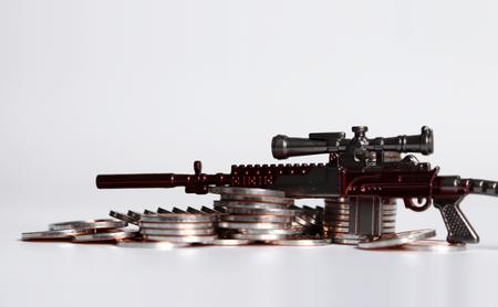 A miniature gun on a pile of coins.