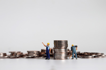 Miniature workers carrying piles of coins.