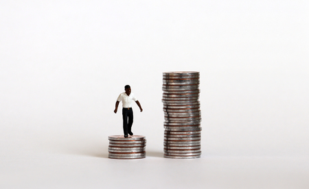 The concept of racial wage discrimination. A miniature black man standing on a low pile of coins.