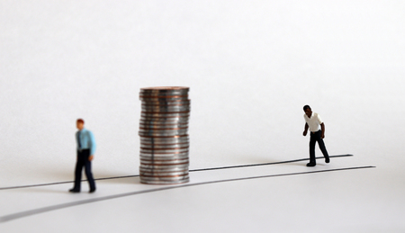 Miniature people and coins. Concepts about racial disparity. 스톡 콘텐츠
