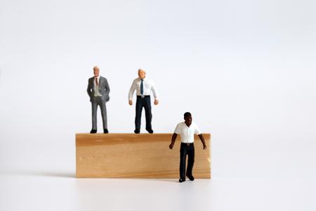 Miniature people standing on tree blocks and miniature man standing under tree blocks.