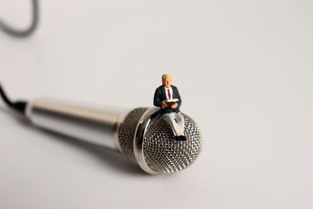 A miniature man sitting on a microphone reading. 版權商用圖片