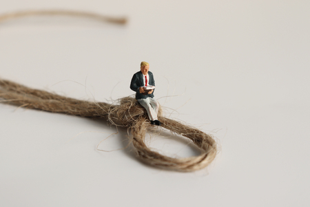 A miniature man sitting on a strapped rope and reading.