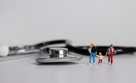 A family of four miniatures with stethoscope. 版權商用圖片